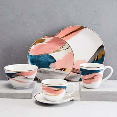White dinnerware set with dark teal, blush pink and mod grey brush strokes and band of gold around the edge of each piece.