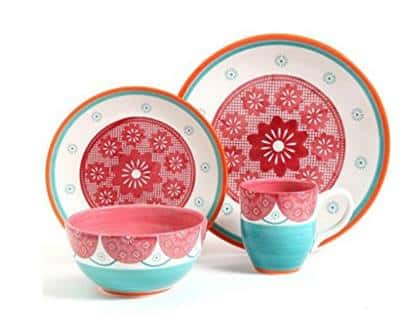 Dinnerware set with white base and papel picado-inspired red design on the center of the plate, with blue sunbursts going around the plate and blue and orange bands running around the edges of the plate.