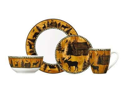 Dinnerware set with silhouetted woods scenery, including a log cabin and woodland animals.