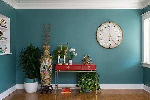 A large white and gold clock hangs on a wall with white trim painted in The Green Hour, Dunn-Edwards' 2018 pick for Color of the Year. A red desk and two pots with plants accessorize the room.