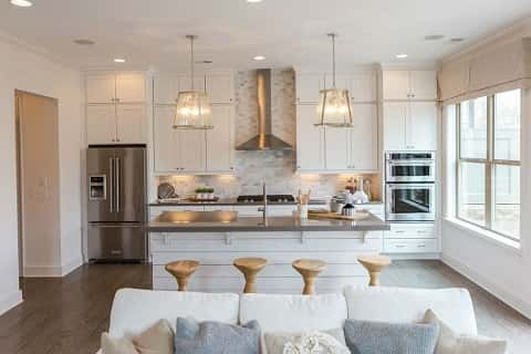 White shiplap accents a kitchen island in this kitchen with a stainless steel range hoods that contracts with all-white wood cabinets. By Edward Andrews Homes.
