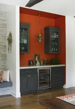 A bar area with black cabinet and an orange accent wall in an entry area is one way to use orange and black in the home in a sophisticated way.