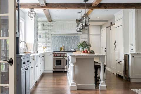 This farmhouse kitchen employs many trends for kitchens in 2018, including exposed wood beams, undermount sink and an all-white color scheme. Designed by Taryn Emerson. Photography by Jared Bumgarner.