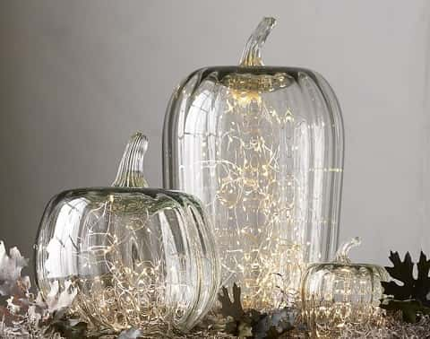 Blown-glass pumpkin cloches with small string of lights inside and fall accessories like fallen leaves around the base.