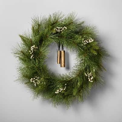 An artificial pine wreath with white berries and a bell from the Hearth & Hand with Magnolia line from Target.
