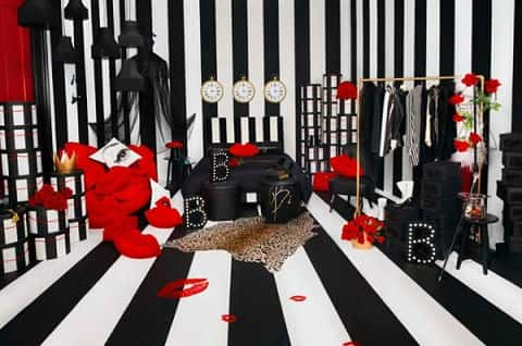 A room with black and white stripes on the walls includes black and red items from IKEA's Omedelbar line, designed by fashion activist Bea Åkerlund.