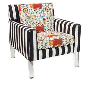 A chair from Iris Apfel's home line with HSN with white and black stripes and floral and circus tent pattern on the cushions.