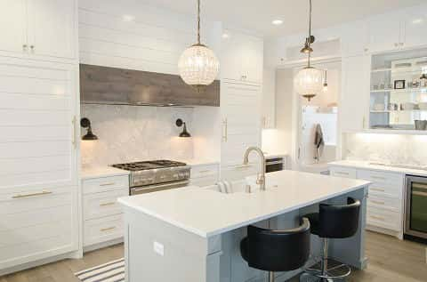 A kitchen with white cabinets white kitchen island and hanging glass pendant lights and wall & Revealing 2018 Kitchen Trends | NewHomeSource
