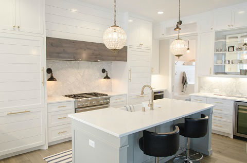 A kitchen with white cabinets, white kitchen island and hanging glass pendant lights and wall sconces hanging above each side of a stainless-steel stove is just one example of layered lighting.