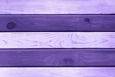 A light Ultra Violet wood plank hanging on a wall has a textured graining.