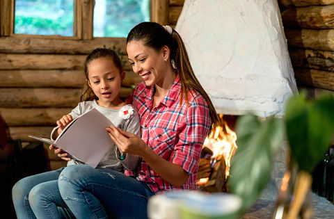 Loving mother reading a book to her daughter at their cozy home by the fire.