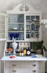 An old secretary painted with a faux finish is set up as a bar on top with niches and drawers for storing coasters, cocktail napkins, candles and table linens.