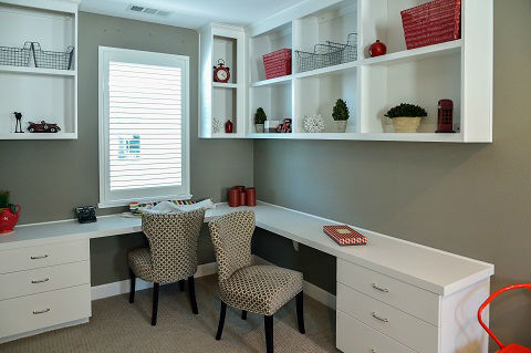 A modern study room interior has a desk and cabinets for storage and to keep the space organized.