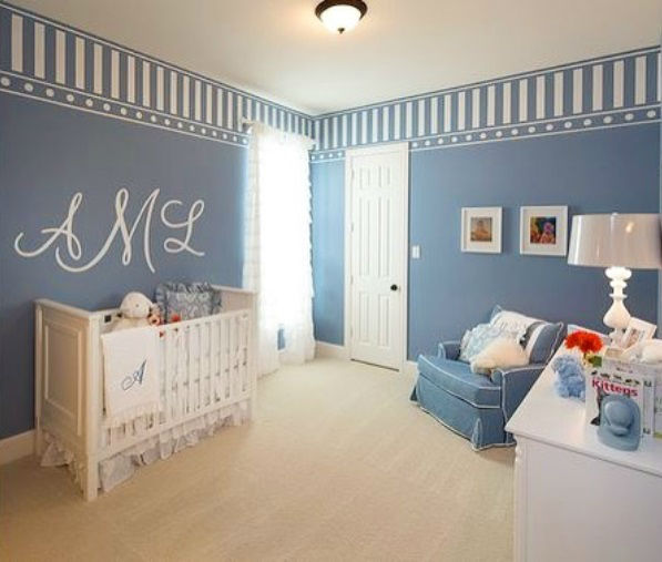 A baby nursery in a new home by Highland Home decked out in blue and white has a calming effect for the new baby.