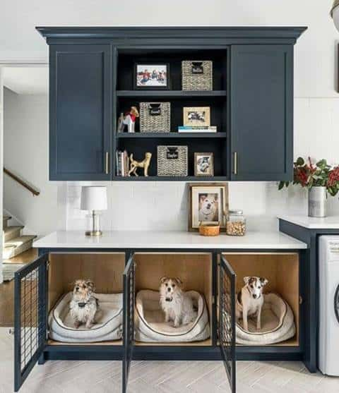 This mudroom by M House Development includes navy blue cabinets, a clothes washer and dryer and a white countertop atop three small dog kennels
