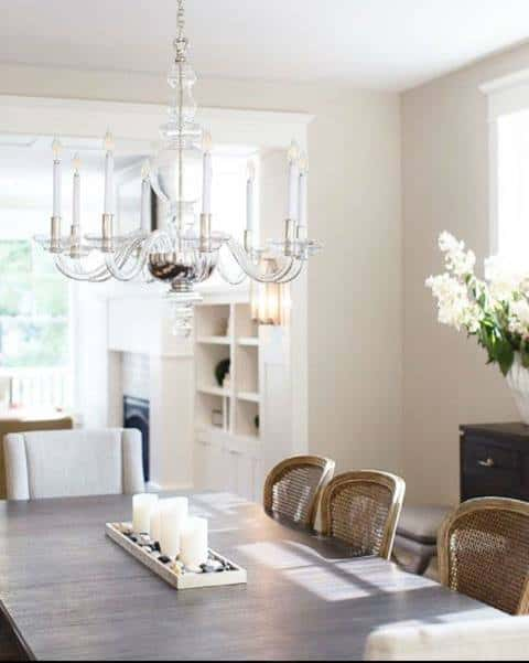 A clear-glass chandelier with faux glass candles hangs above a wood table that seats 8 with three small candles sitting amongst pebbles and a buffet table on the side makes this dining room by Mark D. Williams Custom Homes inviting.