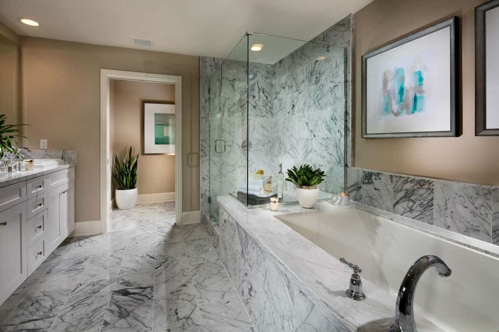 A luxury spa bath like this one in the Plan 3 by The New Home Company at Avanti in Calabasas, CA, includes white marbled tile, a glass-enclosed shower, soaker tub and white double vanities.
