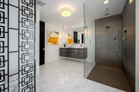 This gorgeous bathroom highlights black in small doses, while adding pops of orange in artwork. White tile and a gray vanity and gray shower soften up the room. Photo courtesy of Ketchum Photography.