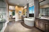 The master bath in a new home by Toll Brothers at The Reserve at Medina in Medina, Minn., uses a neutral wall colors, gray tiles and brown cabinets.