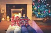 Two pairs of feet with soft, fuzzy Christmas socks sit on a table in front of a fireplace.