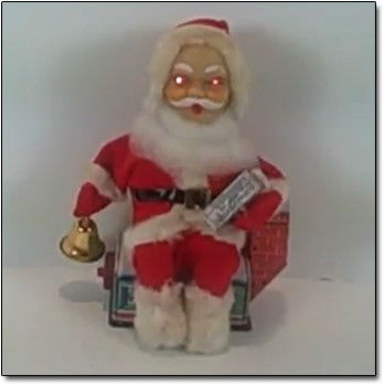 A vintage Santa sits in a chair with a brass bell in one hand and glowing eyes.