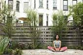 An African-American woman sits in a backyard in a yoga pose, surrounded by her yard's wooden fencing, trees and rocky landscaping.