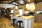 This manufactured home has a kitchen island with white cabinets, multicolored wood flooring and wood planks on the ceiling, providing high-end options. In addition, this manufactured home provides optimal energy efficiency.