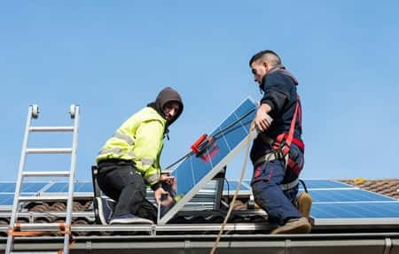 A crew installs solar panels on a home.