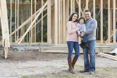 A Hispanic family with a 3-year-old daughter, at the construction site where their new home is being built. They are smiling and looking at the camera, the couple holding their child between them, excited that they will soon be home owners.