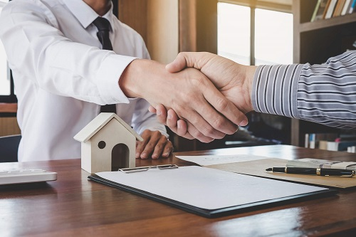 Two men shake hands over a mortgage agreement