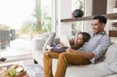 Young man and woman laying on couch in new home, looking at iPad