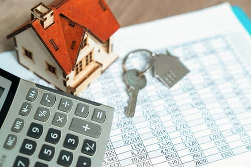 Calculator and house keys sit on top of financial documents