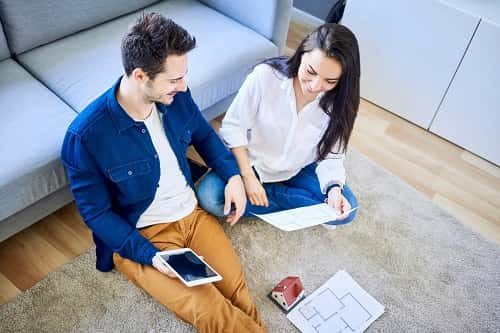 Young couple sitting on floor near couch going over financial documents