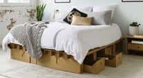 A bedframe and set of under-bed drawers by Karton is made of cardboard and is durable, sustainable and affordable. A queen-sized bed with white duvet, gray quilt and a cardboard night stand are in a bedroom with white exposed brick walls.