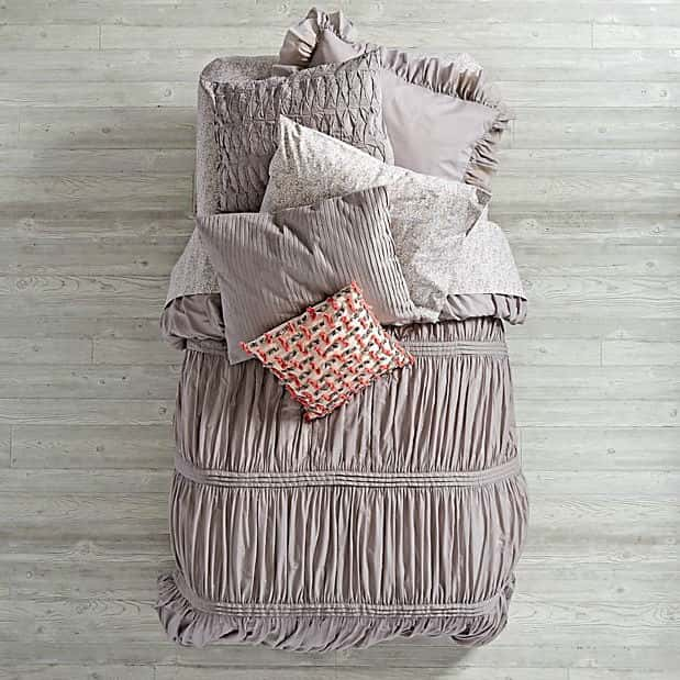 A gathered quilt from the Land of Nod in gray can be reversed to reveal a pink floral print.