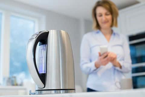 A smart kettle sits on a counter in the foreground, while a woman in the background controls the kettle with a smartphone.