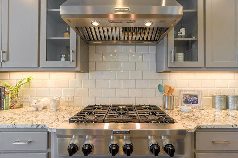 Close-up shot of a stainless steel gas cooktop and stainless steel range hood and white subway tile backsplash in a new home by American Legend Homes at the Lilyana 74s community in Prosper, TX.