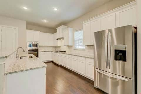 The kitchen in the Fairview plan by Terrata Homes has white cabinets and stainless steel appliances.