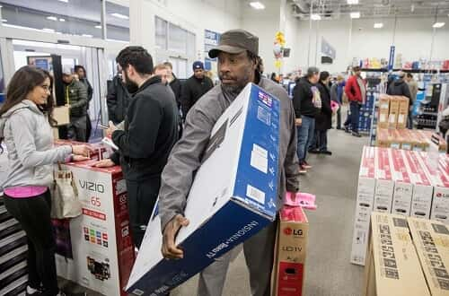 Man in store carrying box on Black Friday.