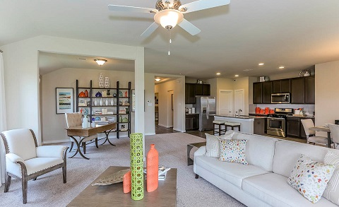 A column helps differentiate an office space from the living room and kitchen in this open floor plan. Model home by Gray Point Homes at Balmoral in Humble, Texas.