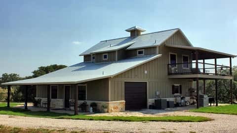 A two-story barndominium by Metal Building Homes is a metal structure with barn space and is surrounded by open space.