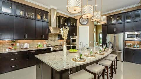 The kitchen in the Francesco IV Plan by Taylor Morrison has a plethora of black slab cabinets, a tan subway tile backsplash, a stainless steel range hood and a large kitchen island with seating for five. At Legacy Estates at Esplanade on Palmer Ranch in Sarasota, Fla.