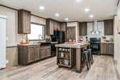 The Anniversary 2.0 plan by Clayton Homes in Donna, Texas, optimizes space in the kitchen with a pantry with wire shelving and a kitchen island with built-in shelves.