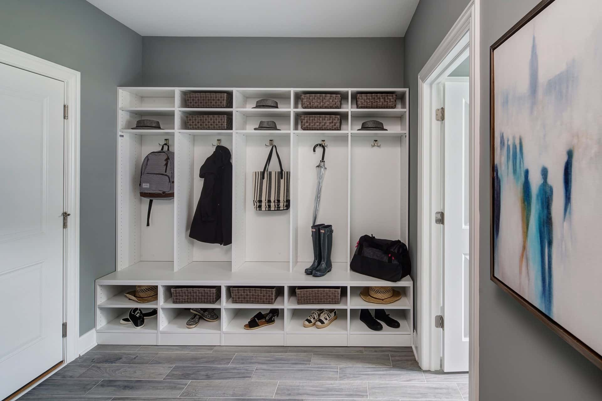 A mudroom with white cubbies and shelves and gray tile flooring in a new home by Lexington Homes at Lexington Towne at Arlington Heights in Arlington Heights, Ill.