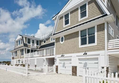 A beach house with a sand-colored exterior and white detailing.