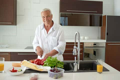 An older man chops veggies on a large white kitchen island in his contemporary kitchen with flat-front cabinets.
