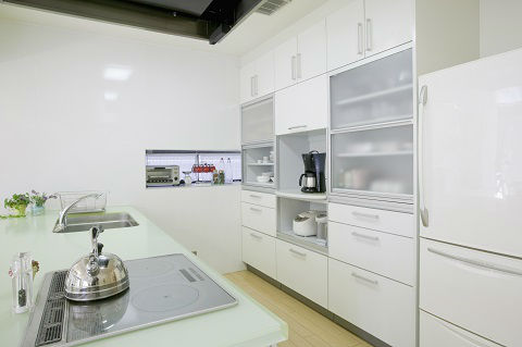 This kitchen has white, flat-panel cabinets, along with an electric stove.