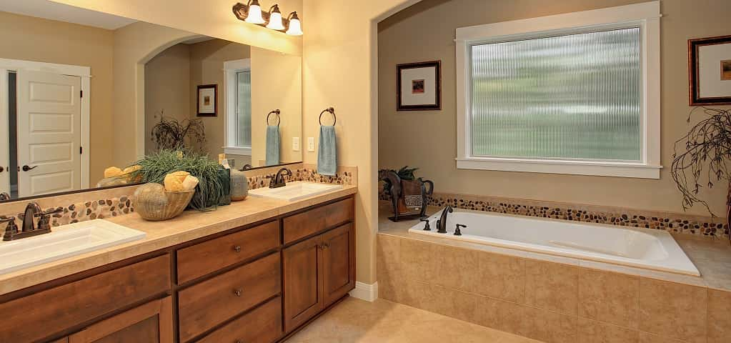 <p>One of the most glamorous aspects of the Adams plan is its five-piece master bath. A large soaking tub, tucked beneath a creamy archway boasts generous side seating. Sitting adjacent to a double vanity, river rock trim helps maintain continuity across the units. <br /> <br /> White double doors separate the en-suite bathroom from the master bedroom, offering the option of light and noise control for a sleeping partner. Not pictured, a separate shower is also part of this space, with a customizable option being a popular upgrade.</p> <p >PHOTO COURTESY OF<br /> Garrette Custom Homes</p>
