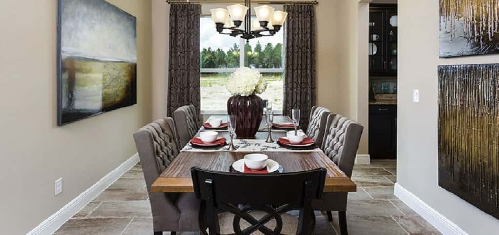 "This dining room means business. Big enough for a 12-person table, it's also offset from the home so that normal traffic doesn't have to navigate around a bulky table, says Jackson.<br /> <br /> Situated lengthwise, the large table is accented by a mural of equal size. A chandelier helps set the mood, while creamy walls and tufted chairs introduce a level of formality. With easy access to the kitchen via its own walkway, hosts can gracefully move between rooms. ""It adds a level of convenience to any dinner party,"" says Jackson.<br /> <br /> PHOTO COURTESY OF<br /> Royal Oaks Homes"