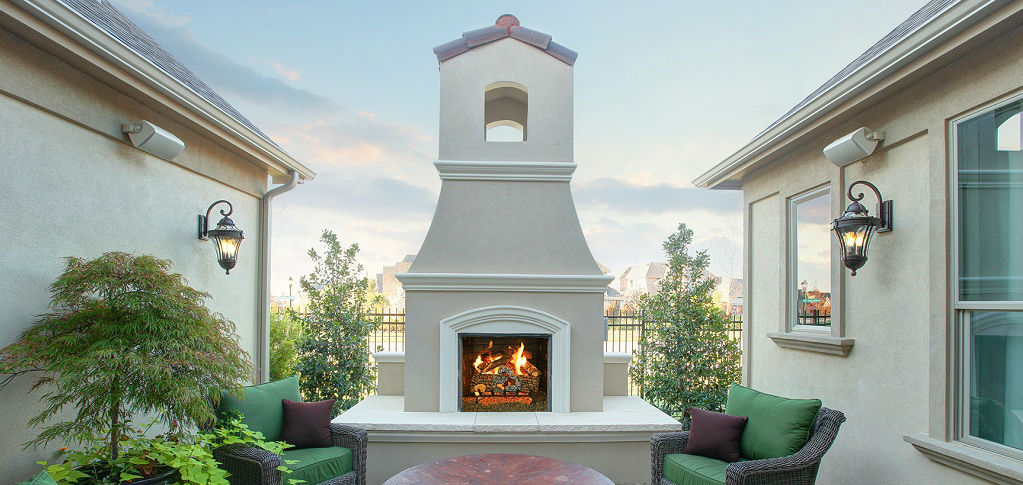 A great chimney in the patio and two wooden armchairs surrounding a round table.